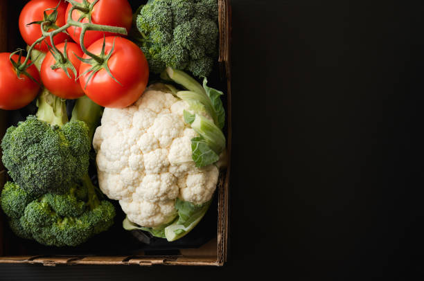 Tomatoes, Cauliflower and Broccoli in Container Close Up, Black Background with Copy Space. Fresh Organic Vegetables, Healthy Eating, Harvesting, Product stock photo