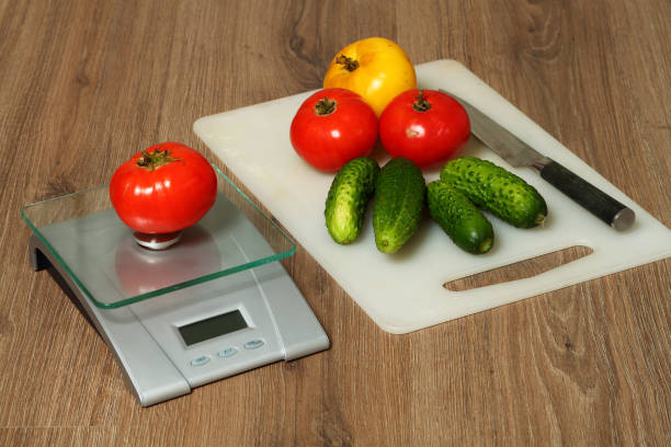 Tomatoes, cucumbers and knife on a cutting Board. stock photo