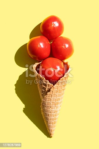 Tomatoes in waffle cones isolated on yellow background