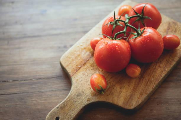 tomates sur une planche à découper - tomate photos et images de collection