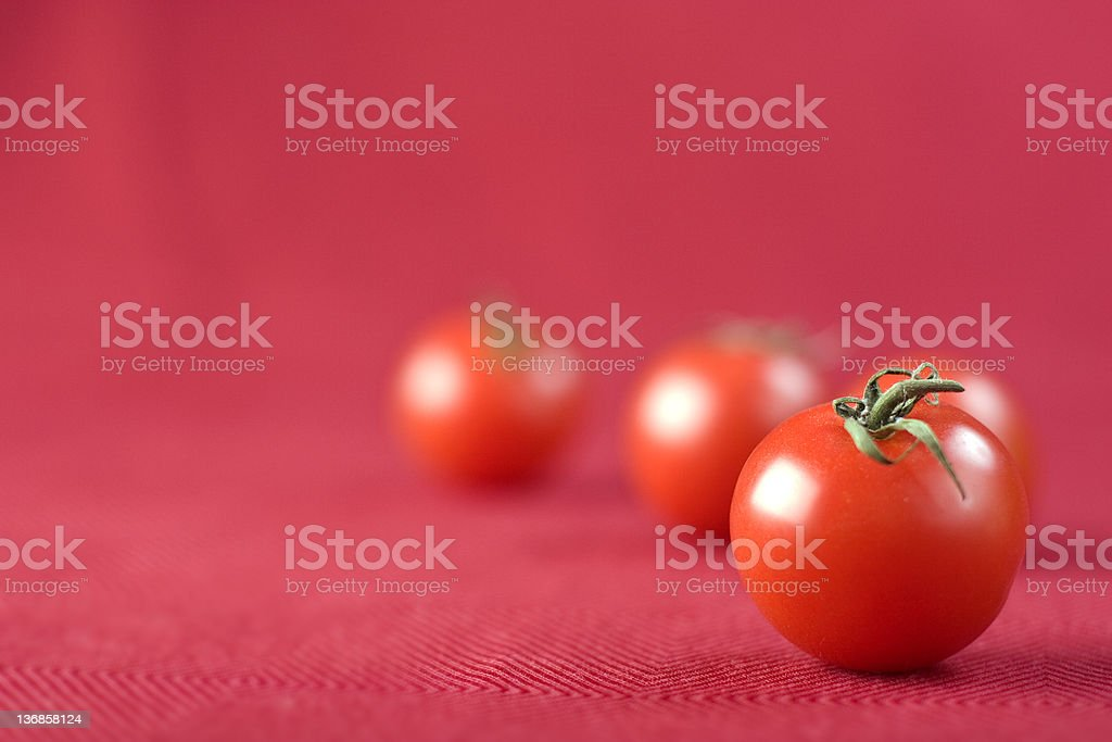 Tomatoes On Red Four small tomatoes on a red background. Color Image Stock Photo
