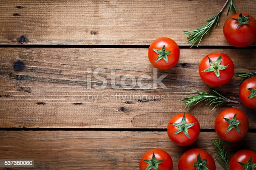 Top view of fresh organic tomatoes on rustic wood background with copy space.