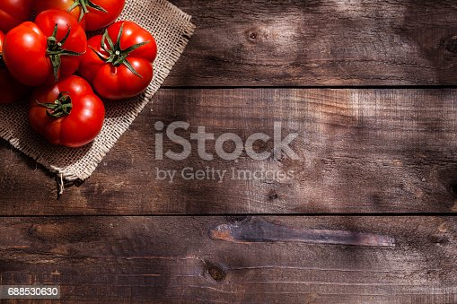 Top view of a small group of red Heirloom tomatoes placed at the top-left corner of a rustic wood table leaving a useful copy space on the table. Predominant colors are red and brown. Low key DSRL studio photo taken with Canon EOS 5D Mk II and Canon EF 100mm f/2.8L Macro IS USM