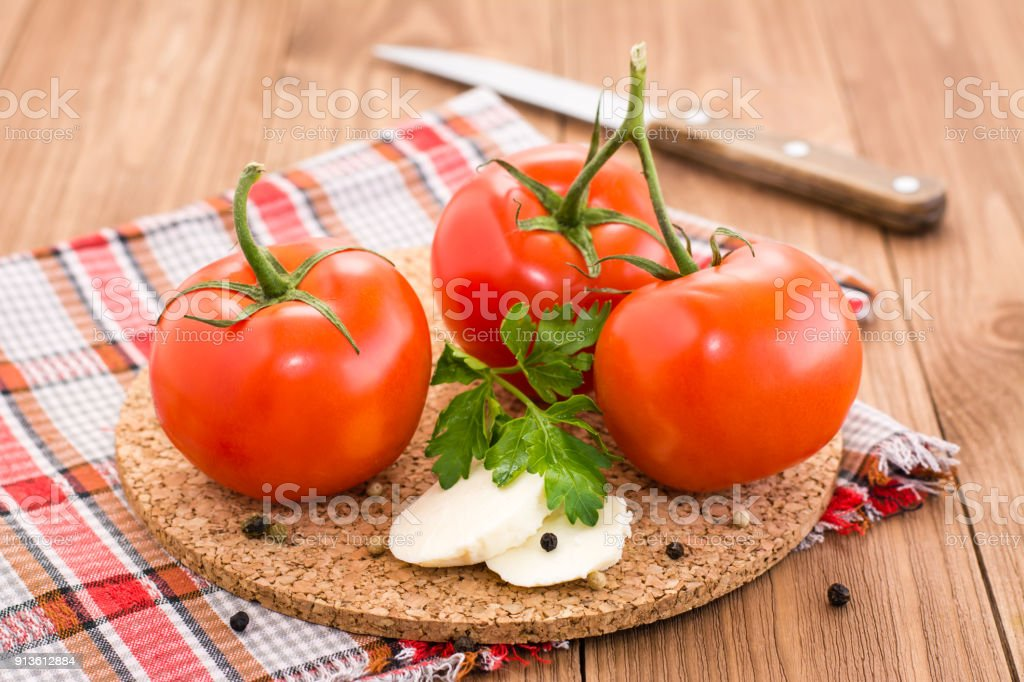 Tomatoes, slices of cheese and parsley on a substrate stock photo
