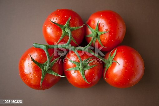 Ripe raw tomatoes with stem. Top view. Studio shot with natural day lighting. Close-up. Indoors.