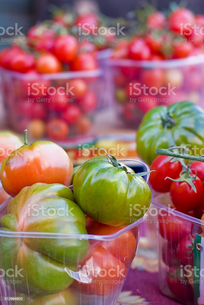 Tomatoes varieties in the steet farmers market Tomatoes varieties - green, red, cherry, on the street farmers market in Catania, Sicily island, Italy. Colorful tomatoes in plastic containers on the street stall. Catania Stock Photo