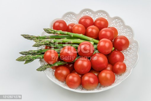Red tomatoes and green asparagus in white plate isolated on white background