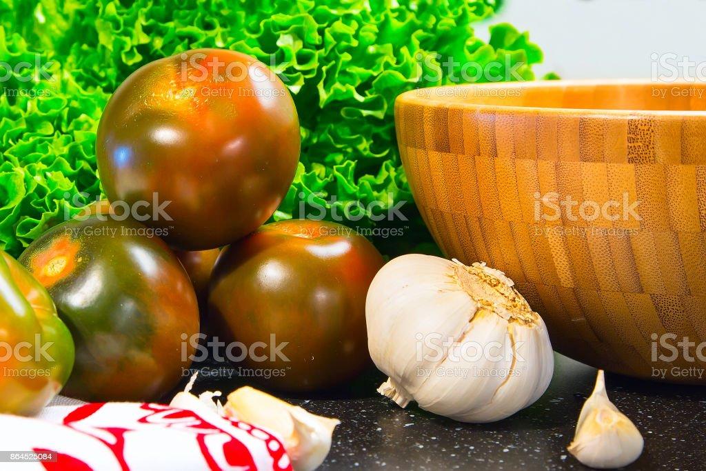 Tomatoes with lattuce, garlic and bamboo bowl stock photo