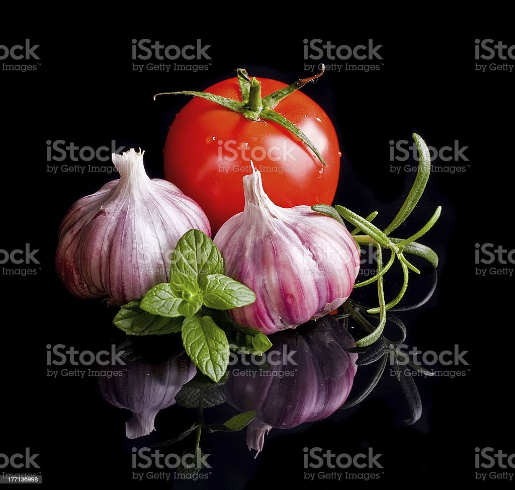 Tomatos and garlic in wooden plate on black background. royalty-free stock photo