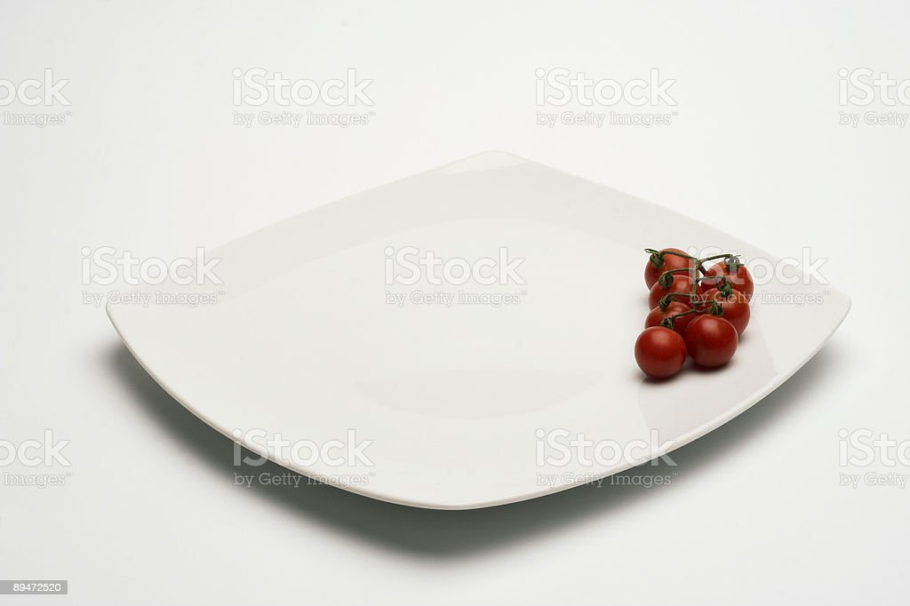 Tomatos in white plate royalty free stockfoto