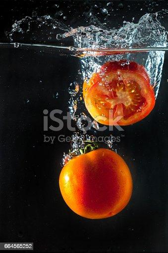 1169153675 istock photo Tomatos splashing with in water 664565252