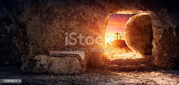 Empty tomb of Jesus at sunrise with crosses in background