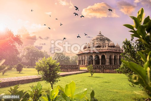 Early mooring Sunrise view of the Tomb of Isa Khan at Humayun's Tomb complex. Birds flying in the colourful sky.