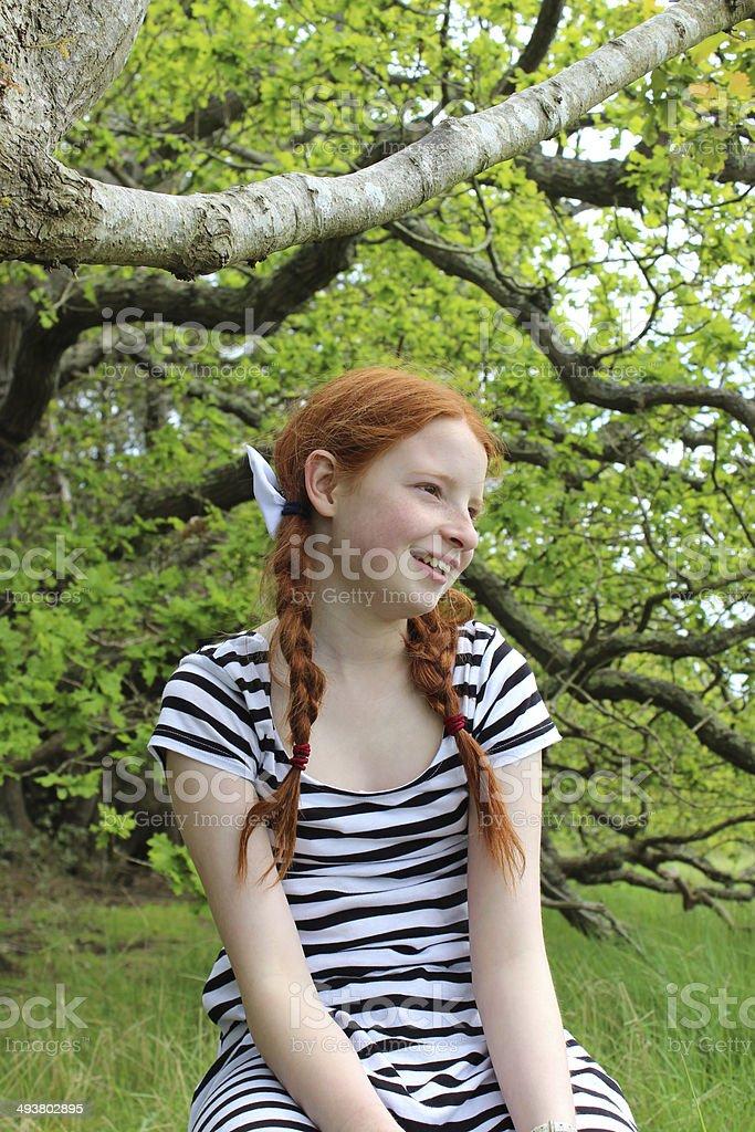 Tomboy girl sitting on branch of oak tree in woodland stock photo