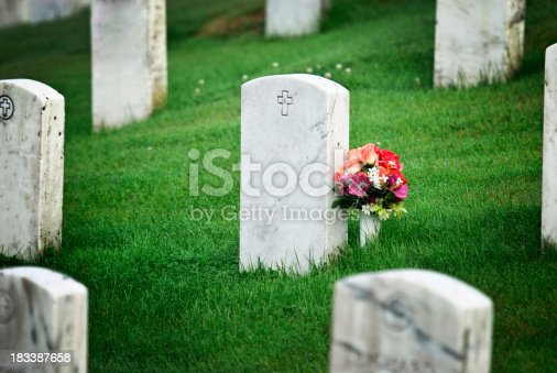 tombstone with flowers in graveyard