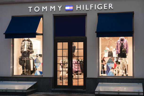 Tommy hilfiger entrance and storefront at night. stock photo