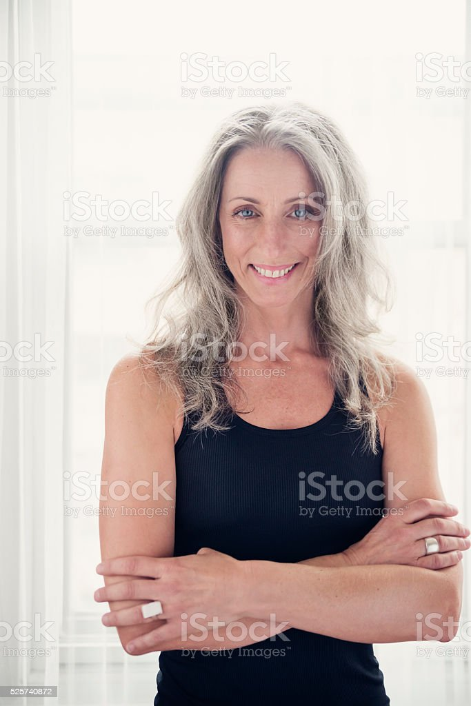 Toned and tanned mature woman with silver hair in tanktop. stock photo