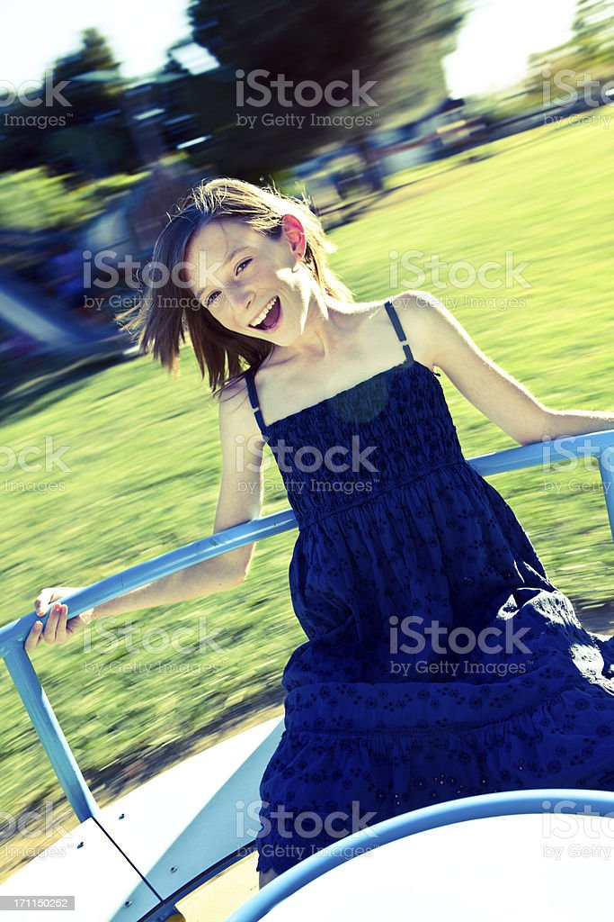 toned beautiful little girl play on carousel at sunny park royalty-free stock photo