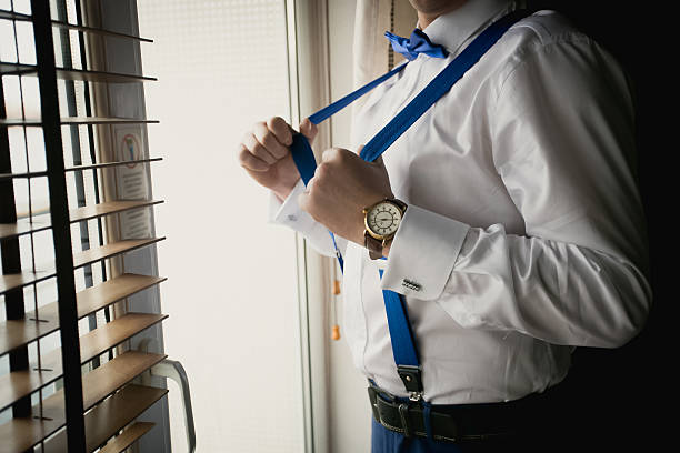 toned closeup of businessman adjusting suspenders at office - pantolon askısı stok fotoğraflar ve resimler