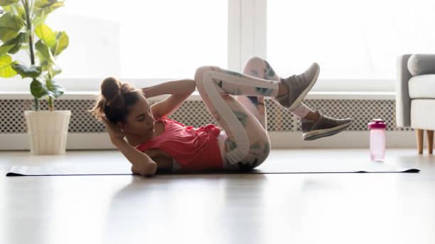 chica tonificada en ropa deportiva haciendo crujidos de bicicleta en estera - músculo abdominal fotografías e imágenes de stock