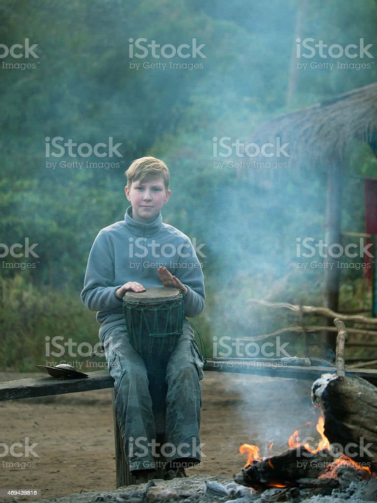 Toned image child sitting on the bench and playing drum stock photo