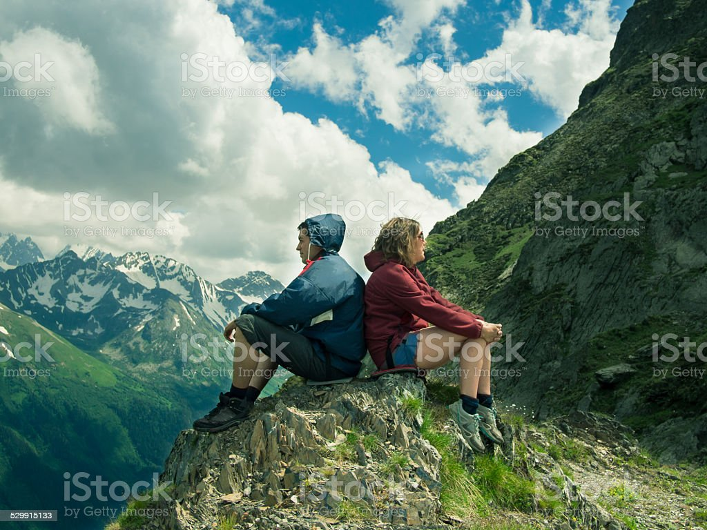 Toned image men and women sitting on the rock stock photo
