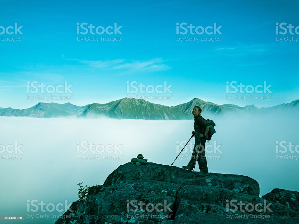 Toned image of an adult woman standing on top mountain stock photo