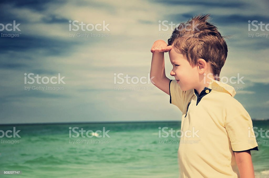 Toned image of boy shielding his eyes from sun stock photo