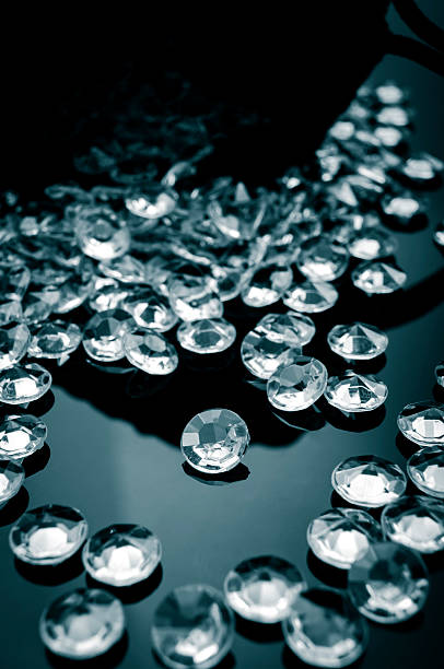 Toned image of diamonds scattered on a shiny surface stock photo