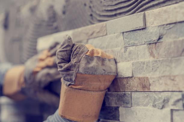 Toned image of hands of tiler worker in gloves stock photo