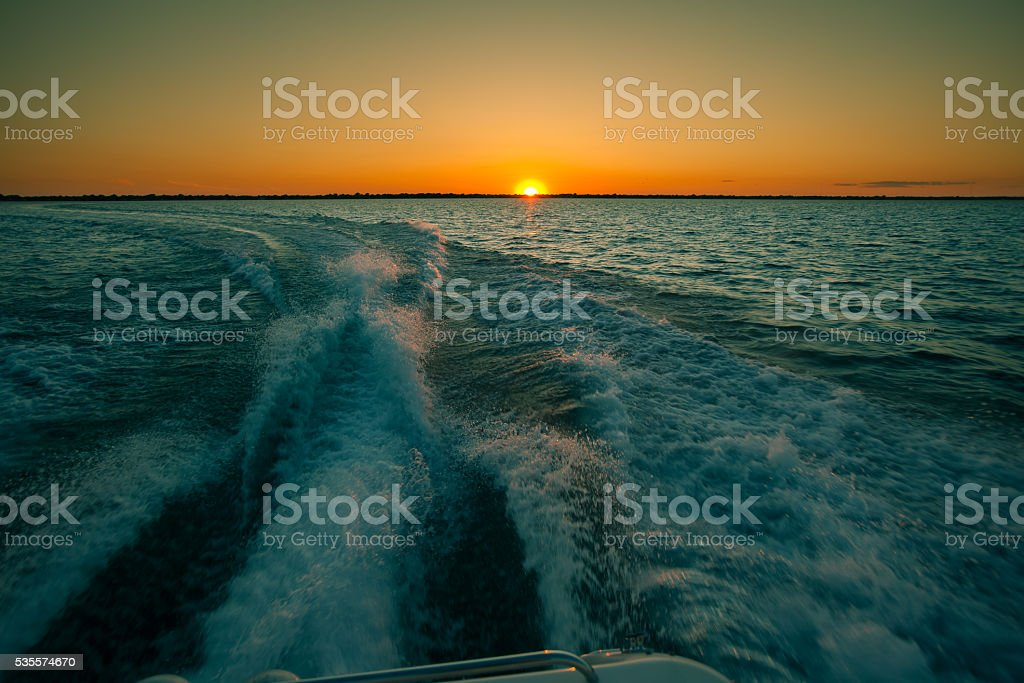 Toned image of lake and sunset with waves from boat stock photo