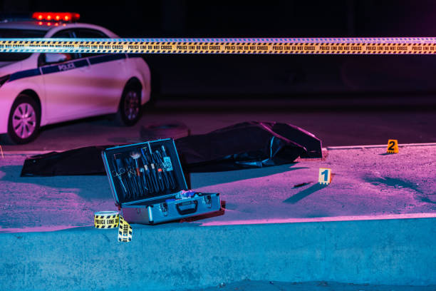 toned picture of case with investigation tools, cross line, police car and corpse in body bag at crime scene stock photo