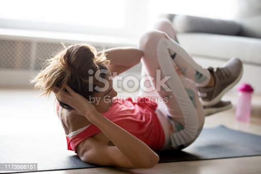 Active toned young woman lying on fitness mat at home doing crisscross exercises working out, sporty girl in sportswear make bicycle crunches toning abs, perform workout. Healthy lifestyle concept