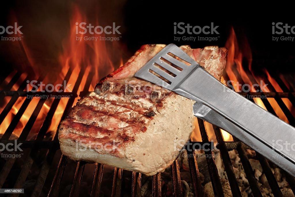 Tongs Holding Grilled Pork Ribs stock photo