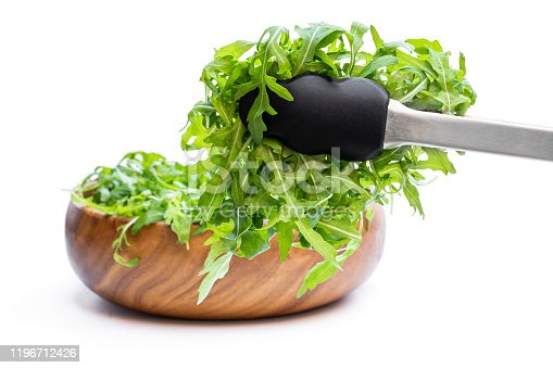 Tongs  with rocket salad leaves isolated on white