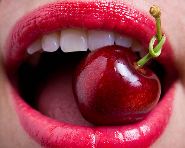 Tongue tied cherry stem, sexy red glistening lips stock photo