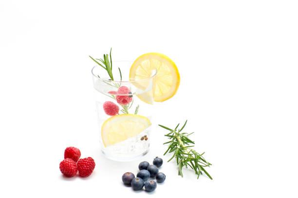Tonic drink with lemon and fruits. White background, studio shot stock photo