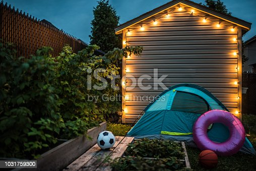 Illuminated shed in the backyard at night. There is a small garden, a camping tent installed,sport balls, a bike and a pink inflatable ring. ids will continue to play tomorrow