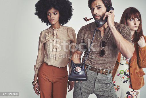 Two attractive young hippies standing behind a handsome man using a retro telephonehttp://195.154.178.81/DATA/i_collage/pi/shoots/797385.jpg