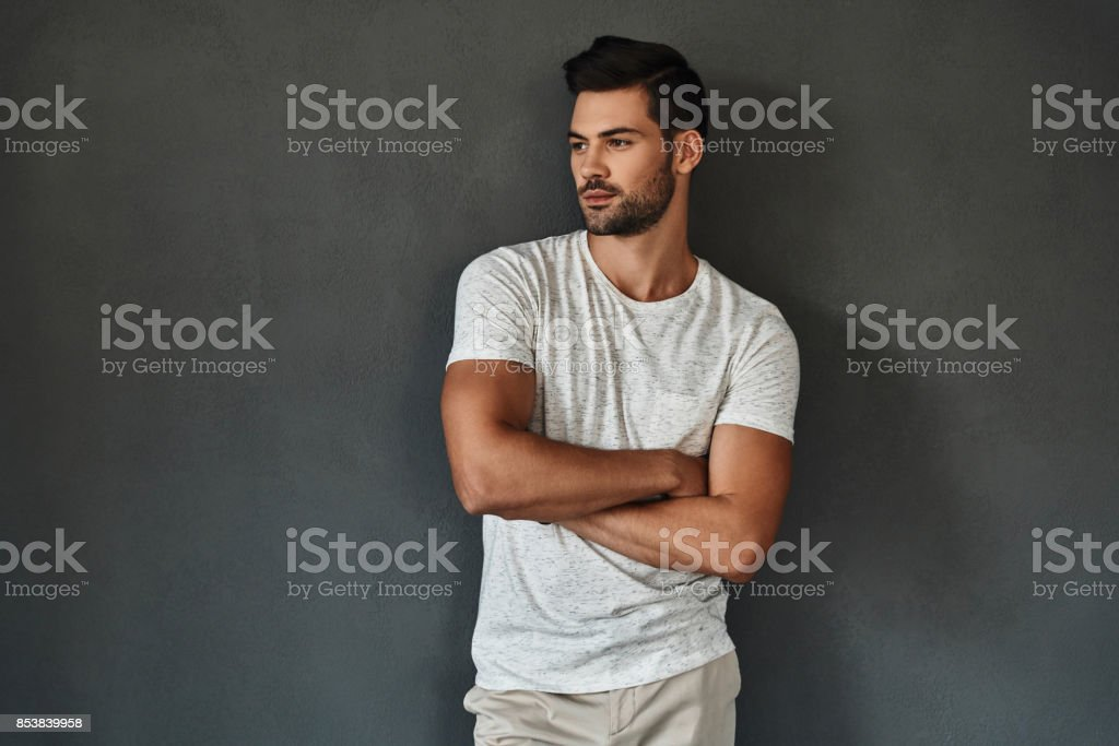 Too good to be real. Handsome young man looking away and keeping arms crossed while standing against grey background Adult Stock Photo