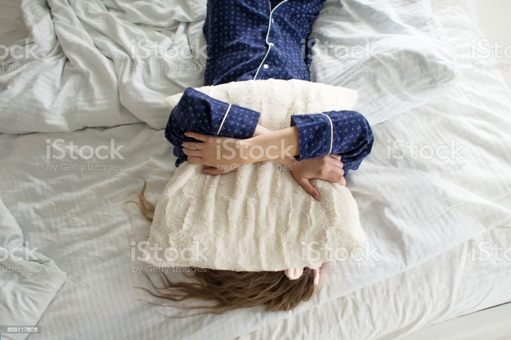 Too lazy to get out of bed, a woman covers her face with a pillow stock photo