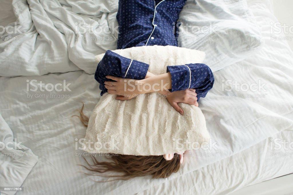 Demasiado perezoso para levantarse de la cama, una mujer cubre su rostro con una almohada - foto de stock