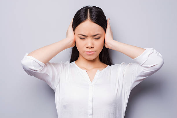 Too loud sound. Beautiful young Asian women covering ears with hands and keeping eyes closed while standing against grey background hands covering ears stock pictures, royalty-free photos & images
