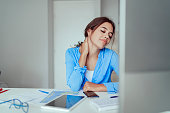 Feeling Tired and Stressed. Frustrated Young Woman Suffering From Neck Pain Massaging her Neck While Sitting at Her Working Place in Home Office