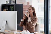 Shot of a young businesswoman suffering with allergies at work
