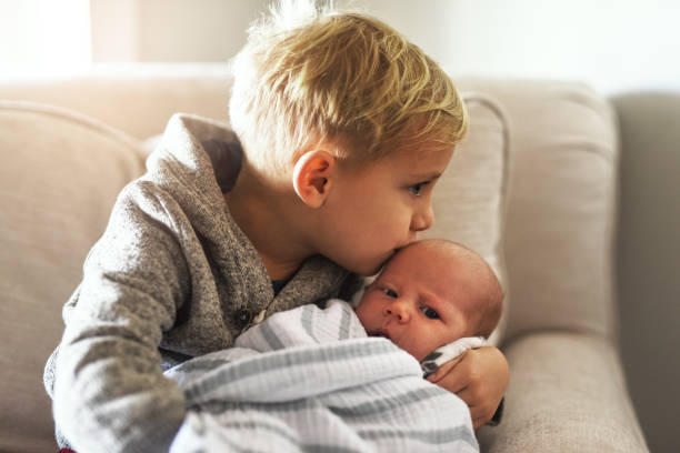 Too much cuteness! Shot of a cheerful little boy holding his little infant brother and giving him a kiss on the forehead while being seated on a sofa at home during the day brother stock pictures, royalty-free photos & images