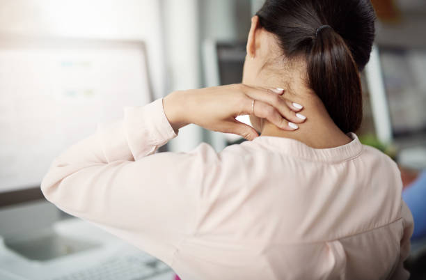 Too much stress, not enough rest Rearview shot of a young businesswoman experiencing neck pain while working at her desk in a modern office bad posture stock pictures, royalty-free photos & images