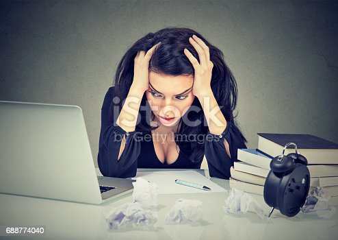 istock Too much work stressed woman sitting at her desk with books in front of laptop 688774040