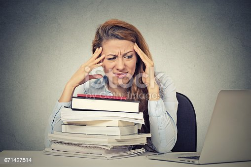 508126619istockphoto Too much work tired stressed young woman sitting at her desk with books in front laptop computer 671427514