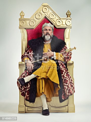 Studio shot of a richly garbed king sitting on a throne